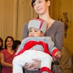 In aceasta imagine il aveti pe cel mai mic manechin Petite Coco, in varsta de numai 5 luni, defiland in bratele mamei lui, intr-un costum Micul General.